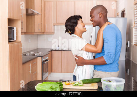 lovely young African couple embracing in kitchen - Stock Photo