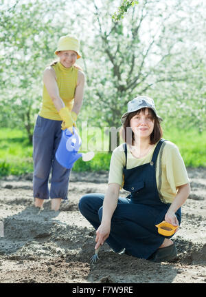 Two  women sows seeds in bed at field - Stock Photo