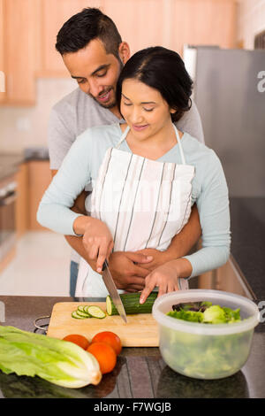lovely young Indian couple chopping vegetables together in the kitchen - Stock Photo
