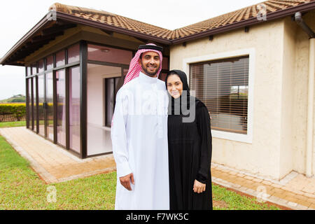 portrait of lovely young Muslim couple standing in front of their house - Stock Photo