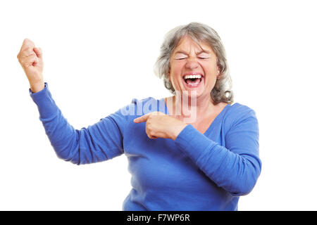 Happy female senior citizen showing her muscles - Stock Photo