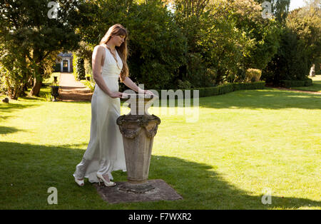 Lady with sundial in white dress on lawn - Stock Photo