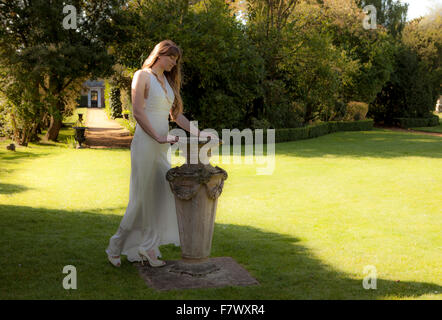Girl on lawn with sundial - Stock Photo