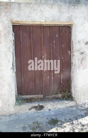 Old wooden door in dilapidated condition on the Greek Island of Santorini - Stock Photo