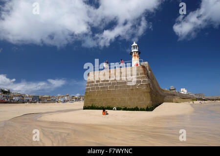 St Ives, Cornwall, UK: Blue sky and fluffy white clouds above a sunny beach around Smeaton's pier - Stock Photo