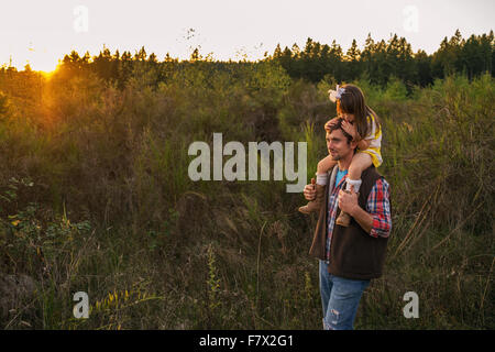 Father carrying daughter on his shoulders in the countryside - Stock Photo
