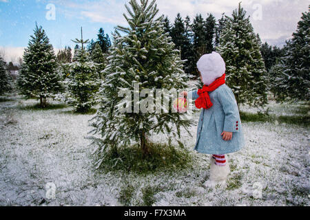 Girl hanging Christmas decoration on a tree outside in the snow - Stock Photo