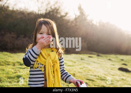 Laughing girl with hand in front of her mouth, holding mobile phone - Stock Photo