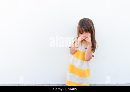 Girl with hands in front of her mouth - Stock Photo