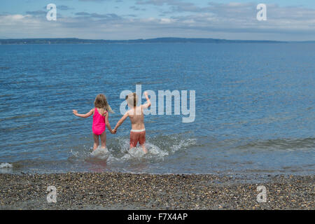 Boy and girl holding hands running into the sea - Stock Photo