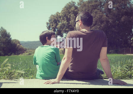 Rear view of father and son sitting on terrace - Stock Photo