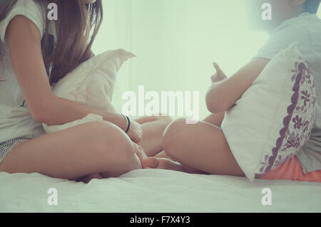 Boy and girl sitting on a bed talking - Stock Photo