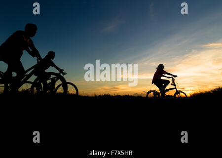 Silhouette of family cycling at sunset - Stock Photo