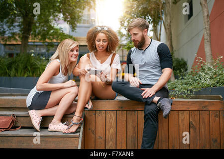 Outdoor shot of group of young adults looking at cellphone. Young friends using mobile phone. - Stock Photo