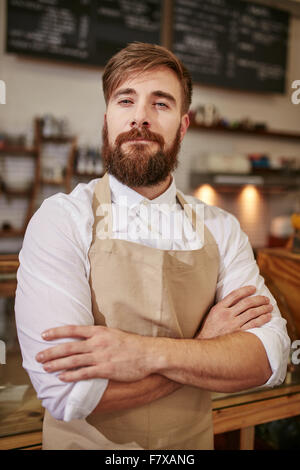 Portrait of young man standing in a coffee shop with his arms crossed. Caucasian man with beard standing in a cafe - Stock Photo