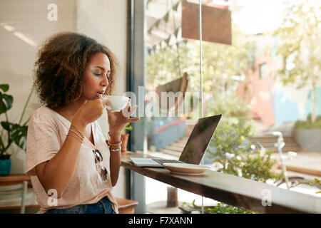 Shot of young woman sitting in a coffee shop with laptop and drinking coffee. African american girl having hot and - Stock Photo