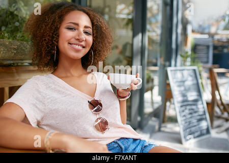 Portrait of young woman drinking coffee. African woman sitting at cafe holding a cup of coffee, looking at camera - Stock Photo
