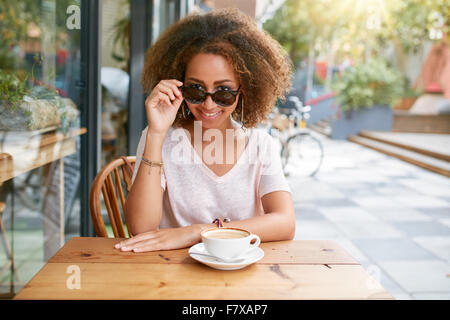 Portrait of pretty young girl at outdoor cafe.  African young woman wearing sunglasses looking at camera. - Stock Photo