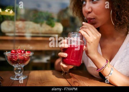 Close up image of young african woman drinking fresh fruit juice while sitting at outdoor cafe. - Stock Photo
