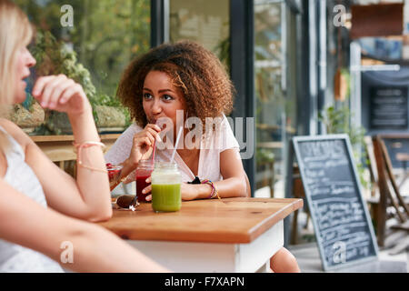 Young african girl drinking juice while chatting with her friend at sidewalk cafe. Female friends meeting at outdoor - Stock Photo