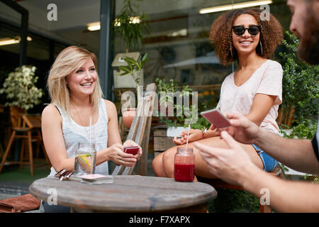 Happy young people playing cards at outdoor coffee shop. Three friends playing poker card game at sidewalk cafe. Stock Photo