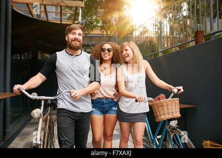 Three young people walking down the street with their bicycles and having fun. Male and female friends with their - Stock Photo