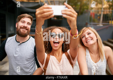 Group of smiling friends taking selfie with mobile phone. Multiracial man and women enjoying themselves outdoors - Stock Photo