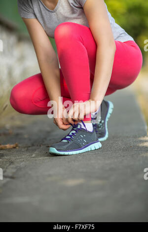 Closeup young sporty girl tying shoelaces on sneakers outdoors. - Stock Photo