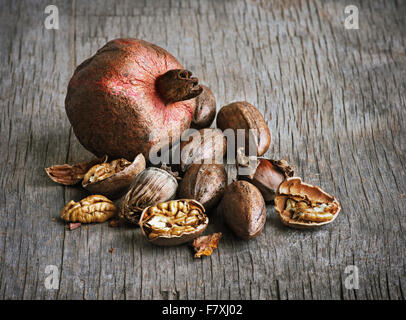 pomegranate and pecan nuts on a wooden table - Stock Photo