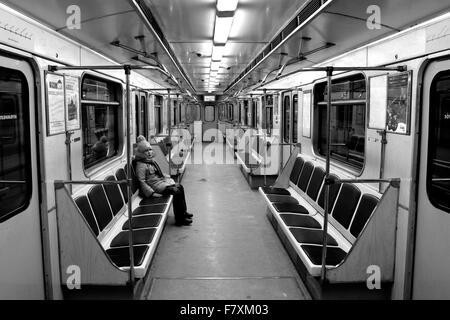 A carriage on the Baku Metro is empty in the evening, with the exception of one girl sitting down.  Image in black - Stock Photo