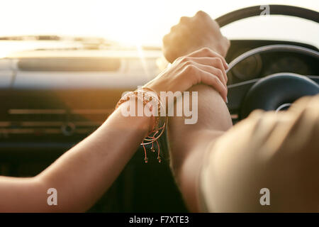 Close up shot of loving couple traveling by car and holding hands. Focus on hands of man and woman in a road trip. - Stock Photo