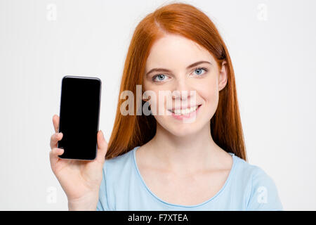Charming cheerful young redhead woman showing blank screen of smartphone over white background - Stock Photo