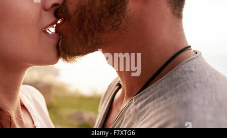 Close up shot of affectionate young couple kissing outdoors. Cropped of young man and woman in love. - Stock Photo