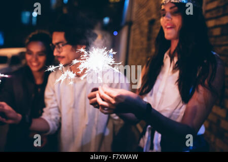 Young friends out at night, celebrating with sparklers. Men and women hanging out at night having a party. - Stock Photo