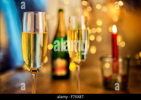 Image of two champagne glasses with bottle, candle and blur lights in background - Stock Photo