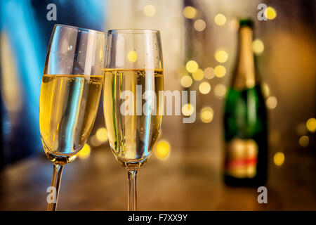 Image of two champagne glasses with bottle and blur lights in background - Stock Photo