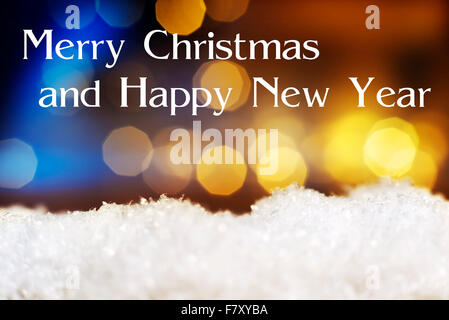 Image of artificial snow and bokeh lights in background and text Merry Christmas and Happy New Year - Stock Photo