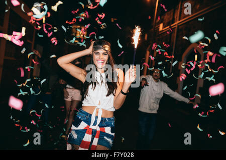 Happy young woman partying with her friends outdoors at night. Friends partying outdoors with confetti and sparklers. - Stock Photo