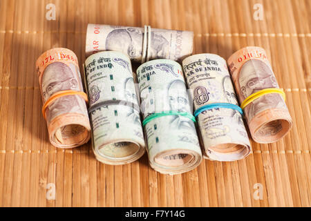 Rolls of Indian rupees on wooden background - Stock Photo