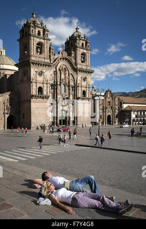 Two tourist rests on the main square in front of the temple of the Company. - Stock Photo