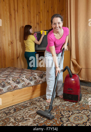 Women are cleans with vacuum cleaner in home - Stock Photo