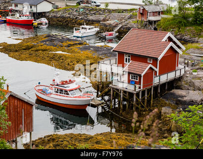 Small house on stilts and small fishing boat moored alongside at Moskenes in the western Lofoten Islands Norway - Stock Photo
