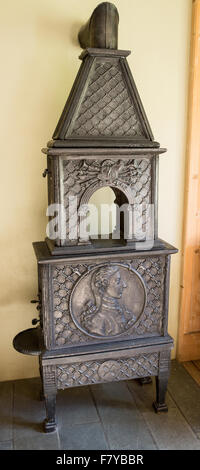 Elegant antique cast iron wood burning stove at the Kongsvold Hotel in Oppland central Norway - Stock Photo