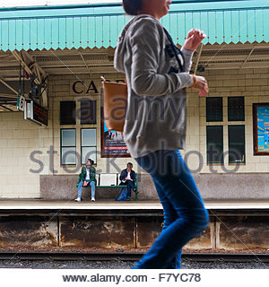 Passengers waiting for the train on Cardiff railway station South Wales UK with a woman in blue jeans walking past - Stock Photo