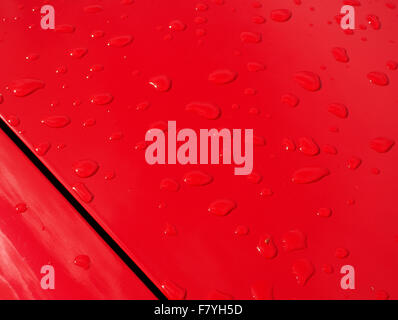 raindrops on bright red bonnet of classic car with gleaming paintwork - Stock Photo