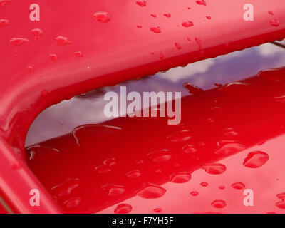 raindrops on bright red spoiler of classic sports car with reflection of cloudy sky in gleaming paintwork - Stock Photo