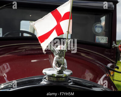 St George's  flag of England flying on bonnet of maroon Essex Super 6 classic car - Stock Photo