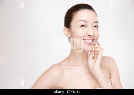 A woman touching her face - Stock Photo