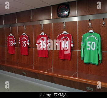 Mix of MUFC shirts hanging up in MUFC dressing room, with MUFC clock, Old Trafford, Manchester - Stock Photo