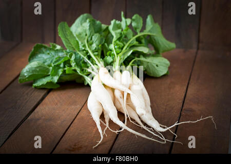 Fresh daikon radish on a wooden background - Stock Photo